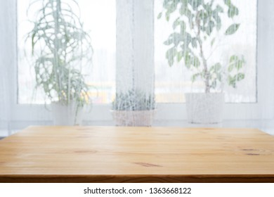 Table and potted flowers against the background of a window, background
