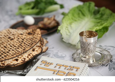Table Ready For Traditional Seder Ritual during the Jewish holiday of Passover. . (Kiddush cup, haggada, matzos, lettuce, an arm)