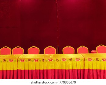 table with red chairs in front of a red wall in a budhist temple in china