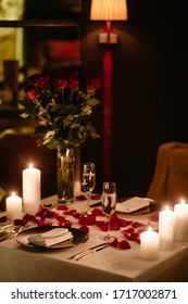 Table for a romantic dinner with two glasses of champagne, red roses and petals