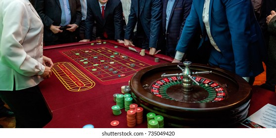 Table with roulette. Group of people on the casino roulette playing