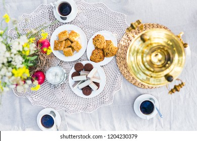 Table with samovar, coffee and sweets decorated with flowers outdoors. Top view. Flat lay