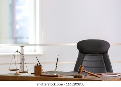 Table with scales of justice and judge gavel in lawyer's office