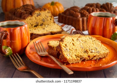 Table scape of homemade pumpkin bread slices sitting on pumpkin plate and mugs of coffee with loaves of fresh baked bread