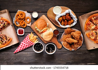 Table scene with large variety of take out and fast foods. Hamburgers, pizza, fried chicken and sides. Above view on a dark wood background.