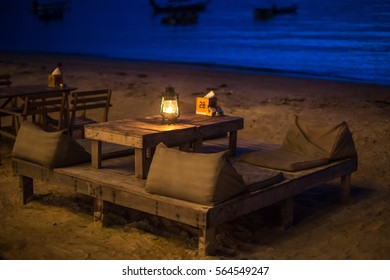 Table in the seafront restaurant at the beach at night. Romantic atmosphere.