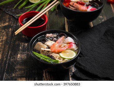 Table served with asian noodle soup in a black bowls with chopsticks, soy sauce, sliced lime and ginger on a dark textured wooden background. Asian style dinner. Close up. Selective focus