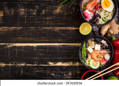 Table served with asian noodle soups in a black bowls with chopsticks, soy sauce, sliced lime, ginger on a dark textured wooden background. Space for text. Asian style dinner. Ingredients for cooking