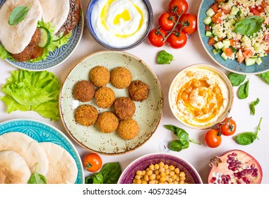Table served with middle eastern traditional dishes. Bowl with falafel, doner kebap, vegetarian pita, hummus, tabbouleh bulgur salad, chickpea, olive oil dip, pomegranate. Top view. Dinner party