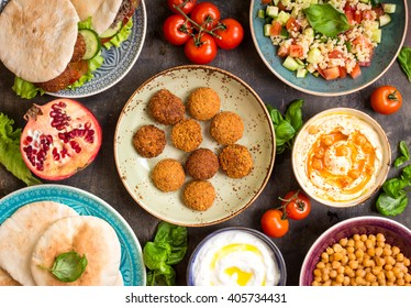 Table served with middle eastern traditional dishes. Bowl with falafel, doner kebap, vegetarian pita, hummus, tabbouleh bulgur salad, chickpea, olive oil dip, pomegranate. Top view. Dinner party - Shutterstock ID 405734431
