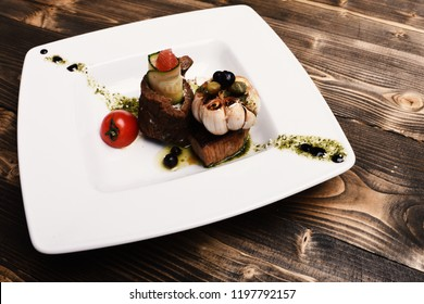 Table served for one in restaurant or cafe. Baked pork steak laid in circle on salad near tomato on wooden background. Dish with modern presentation on square plate. Traditional cuisine concept.