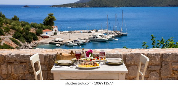 A table served for two with chicken souvlaki and french fries, greek salad, snacks and drinks on the summer terrace of the hotel room by the seascape, beautiful summer greek holidays concept.