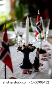 Table set for 17th of May, Norways national day, celebration. Decorated with Norwegian flags. White unlit candle in focus.