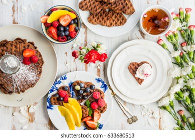 Table set for Breakfast with Homemade Chocolate Waffles in the shape of the Hearts topped with Berries, Rustic Background, Top View