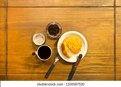 Table set with breakfast, tea, corn cake and jam