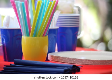 A table set with colorful straws, cups, paper plates, napkins and plastic utensils everything  needed  for a summertime barbecue. Everything except the food.