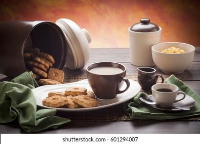 Table set up for continental breakfast: coffee, milk, tea, cookies, corn flakes.