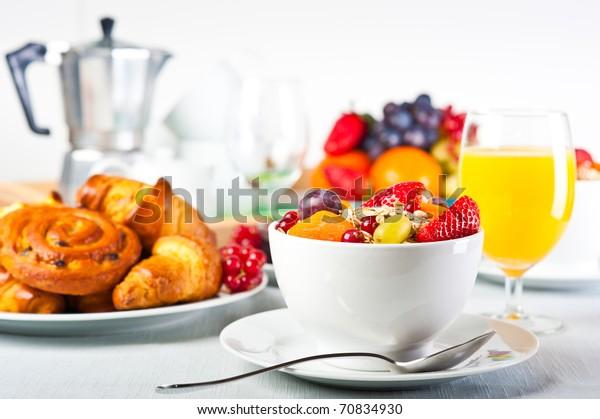 Table dressée pour le petit-déjeuner continental : muesli, fruits et pâtisseries.