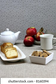 A table set for dessert with cookies, cake and tea