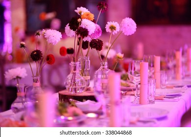 Table set for an event party or wedding reception in purple light