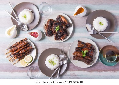 table set of filipino dishes like pork and chicken barbecue, eggplant salad and mango cream graham