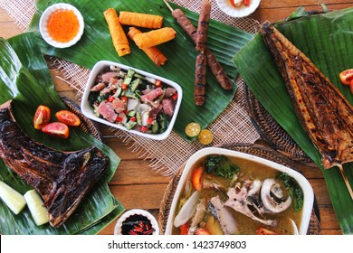 Table Set of Filipino Food: Sinigang, Kinilaw, Shanghai, Longganisa, Grilled Tuna, plus Condiments on Banana Leaf