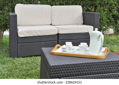 Table set and green garden furniture outdoor ready to enjoy tea time or coffee.