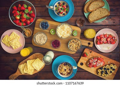 Table set for a healthy breakfast with oatmeal porridge,sweet toast,coconut,peanut butter,chocolate spread,orange juice and fresh berry fruits