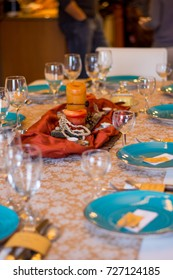 Table set for a holiday dinner party with rustic orange and centerpiece made from candles and natural items