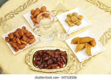 A table set for Iftar, the fast-breaking during the Muslim holy month of Ramadan From the bottom, clockwise, dates, Asabe zeinab or Zeinabs fingers, Awama, kunafeh and katayef pancakes