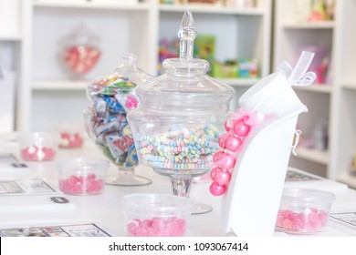 A table is set for a kids birthday party at a candy shop with a pink gum ball necklace for the birthday girl and candy bingo for the kids to play.