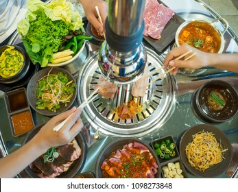 Table of set of korean barbecue, pork, meat, rice, vegetables, sauce and hood, ready for grill