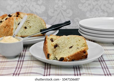 Table set with a loaf of Irish Soda bread with slices on a plate in front.  Side of whipped butter.