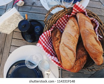 Table set  up for lunch/dinner. Fresh baguette in a basket, sparkling wine bottles on a background. Side view, top view.
