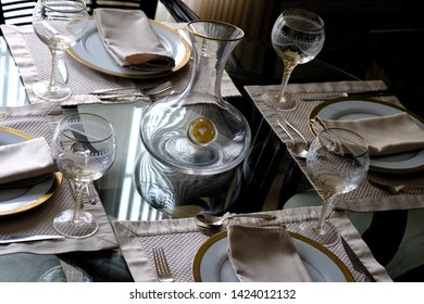 Table set for meal with elegant wine decanter and venetian wine goblets