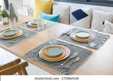 Tisch auf dem Esstisch mit gelber und grauer Tellereinstellung.