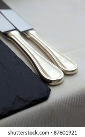 Table set with silverware and plate of slate