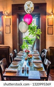 Table set for six persons celebration, indoor, decorated with balloons and colorful flowers