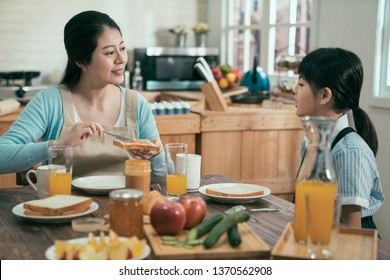Table set for tasty family breakfast with toast butter peanut jam. happy sweet mom and kid sitting at morning health meal at home kitchen. little girl before go elementary school eat delicious meal