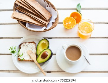 Table set for a typical breakfast with crackers, orange juice, toast, avocado and coffee