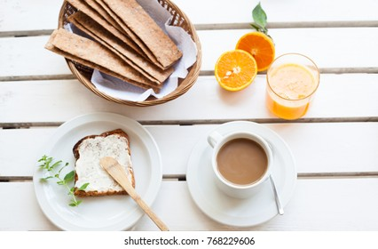 Table set for a typical breakfast with crackers, orange juice and coffee