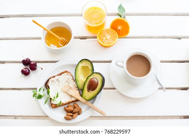 Table set for a typical breakfast with orange juice, toast, avocado and coffee