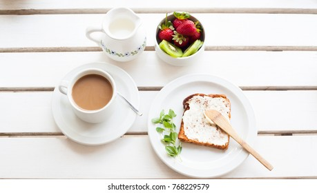 Table set for a typical breakfast with poached eggs, coffee, milk, fresh fruits and toast