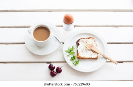 Table set for a typical breakfast with poached eggs, coffee and toast