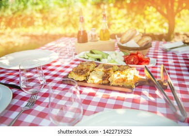 Table is set and waiting for dining in the countryside. Red squared table sheets, Albanian traditional food fresh vegetables and home made pie.