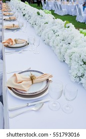 Table set for wedding or event party. Elegant and luxury decoration in soft orange with flowers, silver cutlery, wine glasses, textile napkin.
