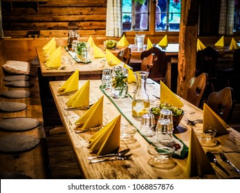 table set with yellow napkins and white empty plates on a wooden table in a rustic restaurant
