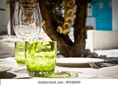Table setting for al fresco dining in a picturesque village street with olive tree and garlic in the background.