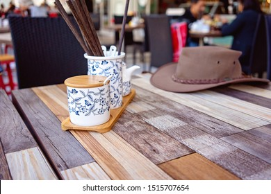 Table setting in an asian restaurant with an aussie style hat resting on the edge