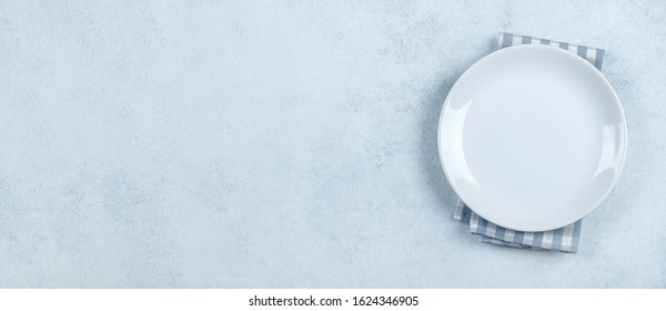 Table Setting Background. Light plate on blue stone table with blue checked tablecloth. Place for text, copy space. Top view, flat lay. Mockup. Banner for website